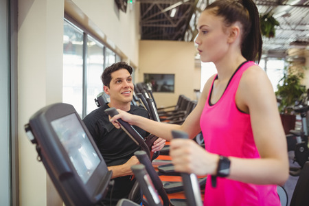 working out: Fit woman working out with trainer at the gym