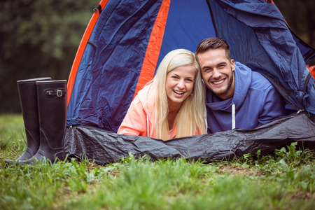 adventuring: Happy couple lying in their tent in the countryside