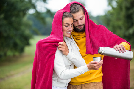 adventuring: Happy couple under a blanket pouring hot drink in the countryside Stock Photo
