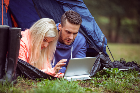 adventuring: Happy couple lying in their tent using tablet in the countryside Stock Photo