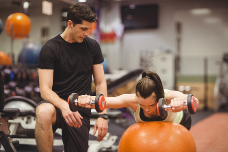 strength training: Fit woman working out with trainer at the gym