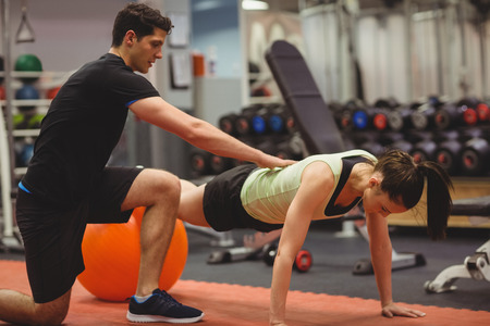 athletics training: Fit woman working out with trainer at the gym