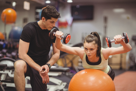 fitness trainer: Fit woman working out with trainer at the gym