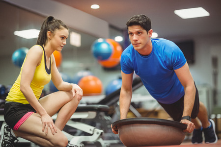 personal trainer: Fit woman working out with trainer at the gym