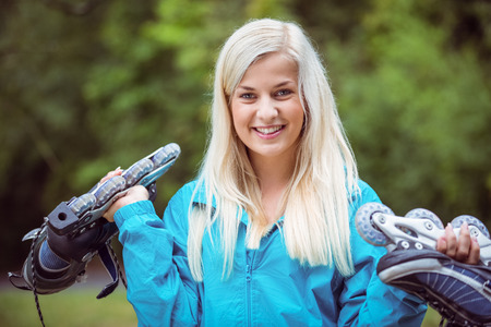 adventuring: Happy blonde holding inline skates in the countryside