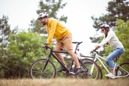 ciclismo: Feliz pareja en un paseo en bicicleta en el campo