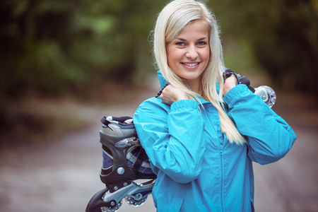 inline: Happy blonde holding inline skates in the countryside