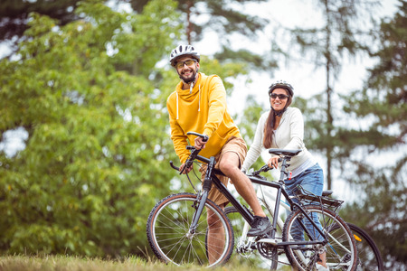 adventuring: Happy couple on a bike ride in the countryside Stock Photo