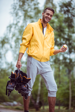 adventuring: Handsome man holding inline skates in the countryside