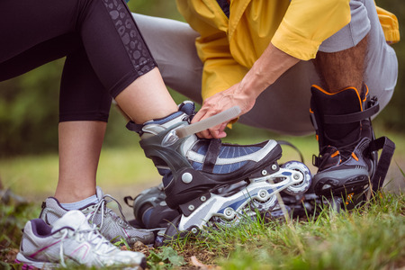 putting in: Happy couple putting on roller blades in the countryside