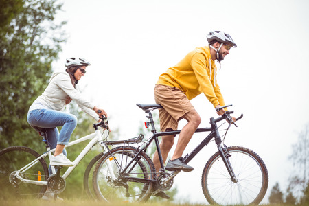 bike riding: Happy couple on a bike ride in the countryside Stock Photo
