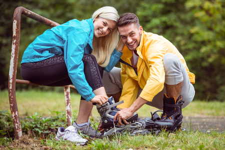 adventuring: Happy couple putting on roller blades in the countryside