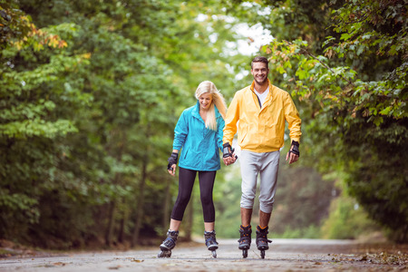 blading: Happy couple roller blading together in the countryside