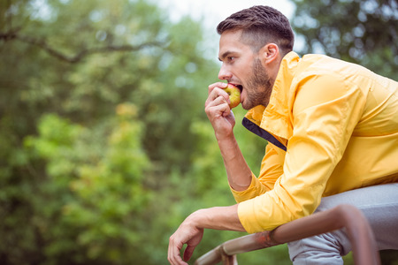 adventuring: Fit man eating an apple in the countryside