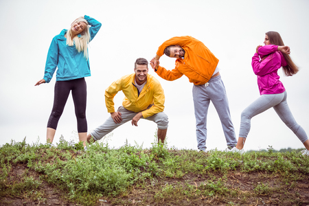 adventuring: Friends stretching before a hike in the countryside