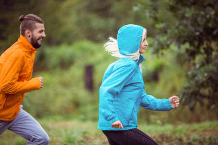 adventuring: Happy couple running on a hike in the countryside Stock Photo