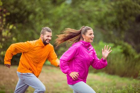 uomo sotto la pioggia: Coppie felici che funzionano su una escursione in campagna