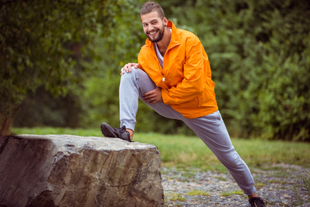 hiking: Man stretching on a hike in the countryside Stock Photo