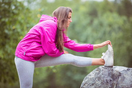 adventuring: Fit woman stretching her leg in the countryside Stock Photo