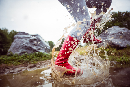 adventuring: Woman splashing in muddy puddles in the countryside