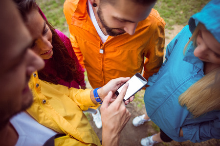 adventuring: Friends using a smartphone on hike in the countryside