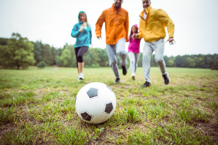 adventuring: Friends running towards football in the countryside