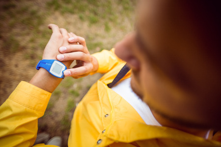 adventuring: Man using his smartwatch on a hike in the countryside
