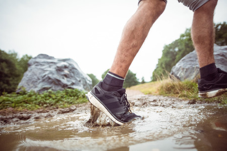 adventuring: Man walking in muddy puddles in the countryside