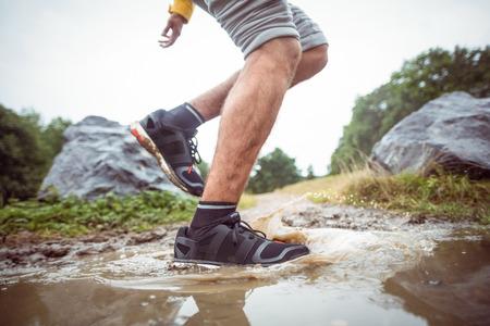 adventuring: Man splashing in muddy puddles in the countryside