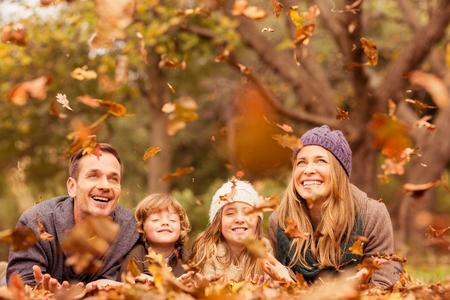 junge Familie Werfen Lächeln verlässt um auf einem Herbste Tag