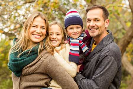 Smiling young family posing together on an autumns day Stock fotó