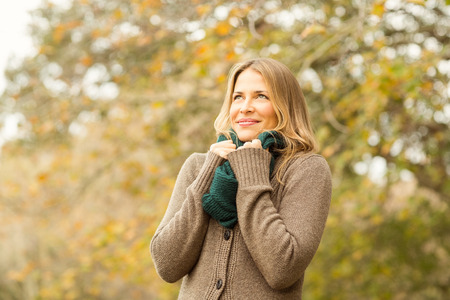 scarf: Smiling woman holding her scarf on an autumns day Stock Photo