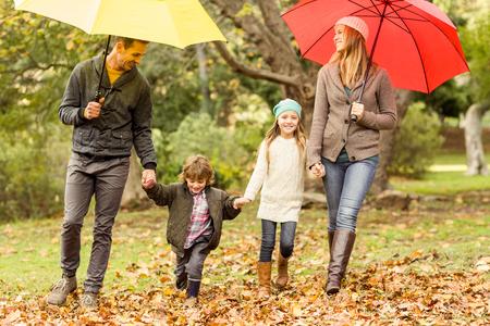 lluvia paraguas: Familia joven sonriente bajo el paraguas en un día otoños