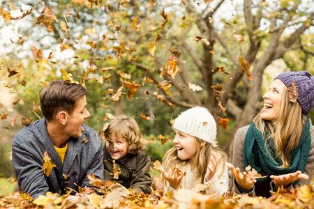 Glimlachend jong gezin gooien bladeren rond op een herfst dag Stockfoto - 46685126