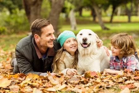 family pet: Smiling young family with dog on an autumns day Stock Photo