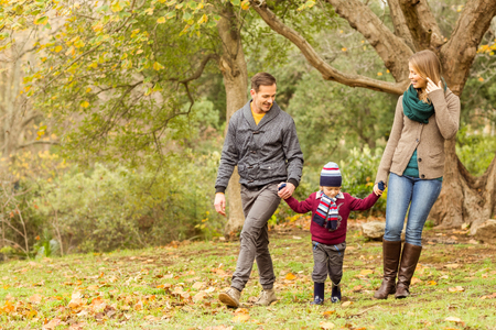 one child: Smiling young family walking together on an autumns day