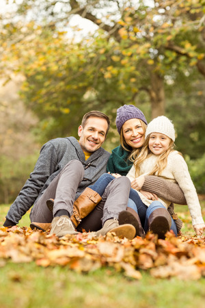 秋の日に葉に座っている若い家族の笑顔