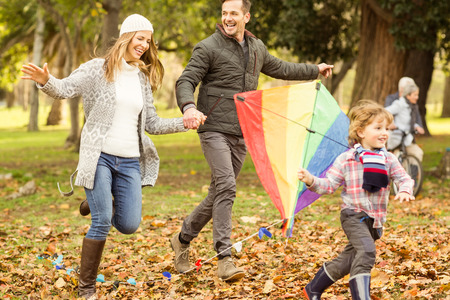 Young family playing with a kite on an autumns day