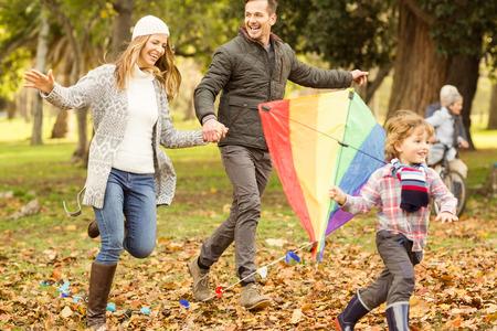 Junge Familie spielen mit einem Drachen auf einem Herbst Tag