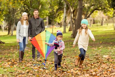 秋の日に凧で遊ぶ若い家族