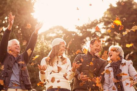 Glückliche Familie werfen Blätter in der Umgebung auf einem Herbst Tag