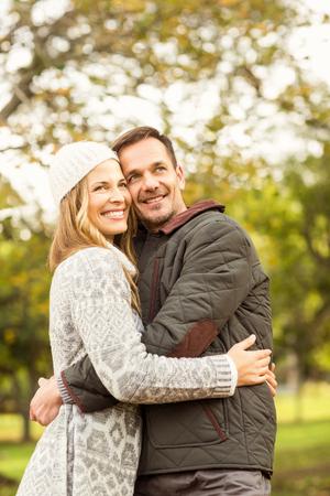 pareja abrazada: Retrato de la sonrisa joven pareja abrazada en un d�a oto�os