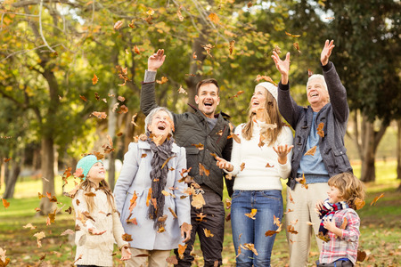 extended family: Happy extended family throwing leaves around on an autumns day