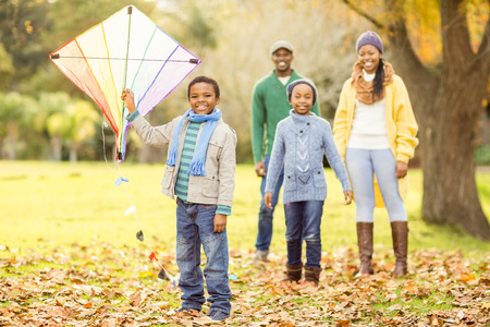 young  family: Young family playing with a kite on an autumns day
