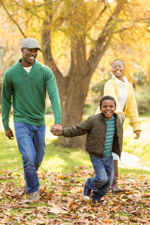 one family: A little boy pulling his parents to walk more quickly on an autumns day