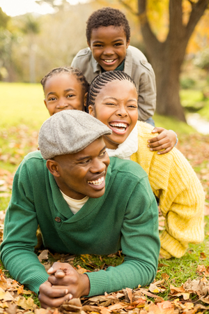 lying on leaves: Portrait of a young smiling family lying in leaves on an autumns day Stock Photo