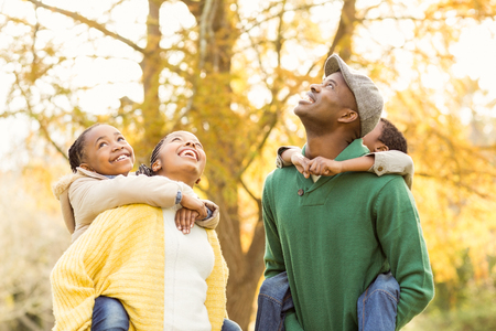 Portrait of a young smiling family in piggyback on an autumns day Stock Photo