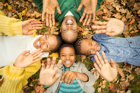 Young family doing a head circles and raising their hands on an autumns day Stock Photo