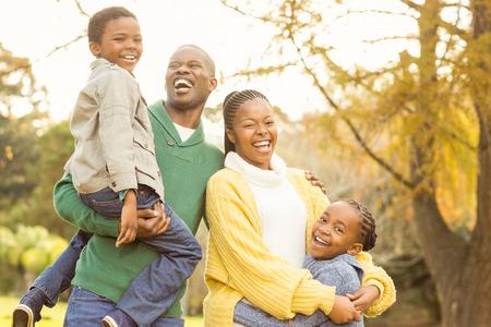 Porträtt av en leende ung familj skrattar på en höst dag