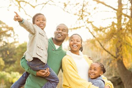 familias felices: Retrato de una joven familia sonriente que señala algo en un día otoños Foto de archivo